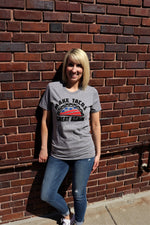 Woman wearing Make Tacos Great Again! printed in USA stars and stripes red, white and blue with a taco across the chest of a unisex soft style short sleeve heather grey t-shirt - Dalton Ink