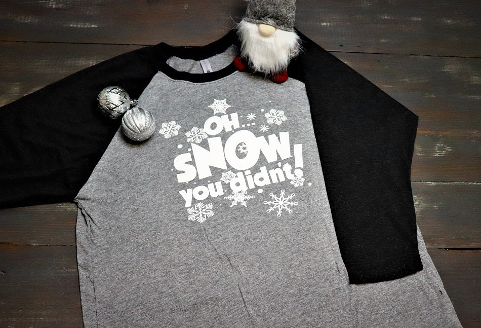 Oh Snow you didn't in white text across the front with snow flakes around it.  Heather grey soft style baseball sleeve unisex t-shirt with black sleeves.  Holiday and Christmas clothing from Dalton Ink