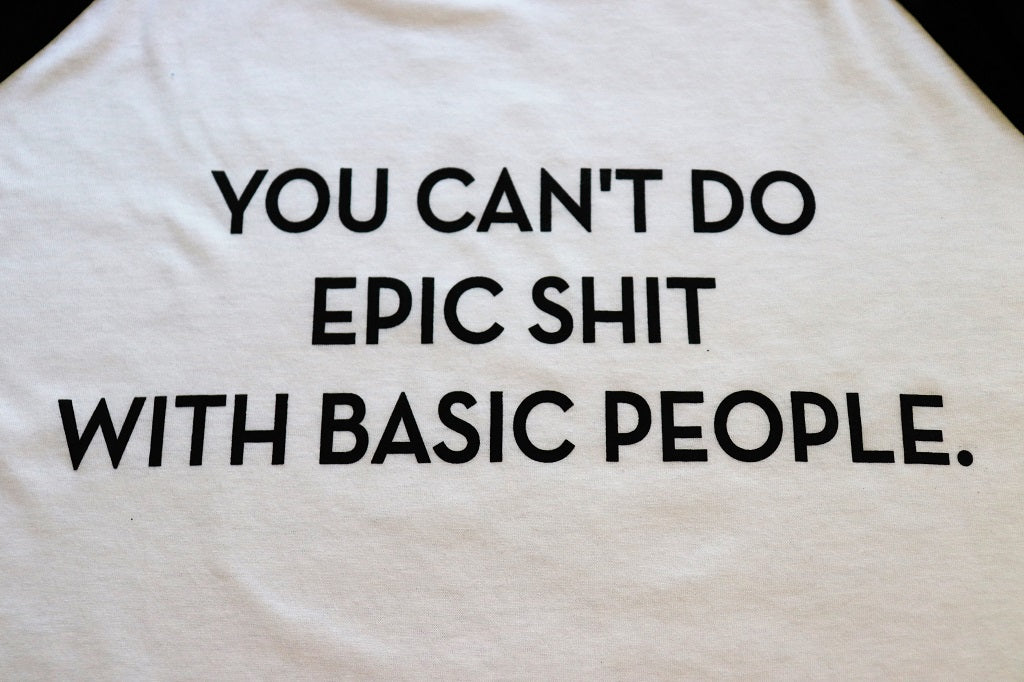 "Close Up of ""You Can't Do Epic Shit with Basic People"" in black text on a unisex baseball crew t-shirt white body and 3/4 black sleeves - Dalton Ink"