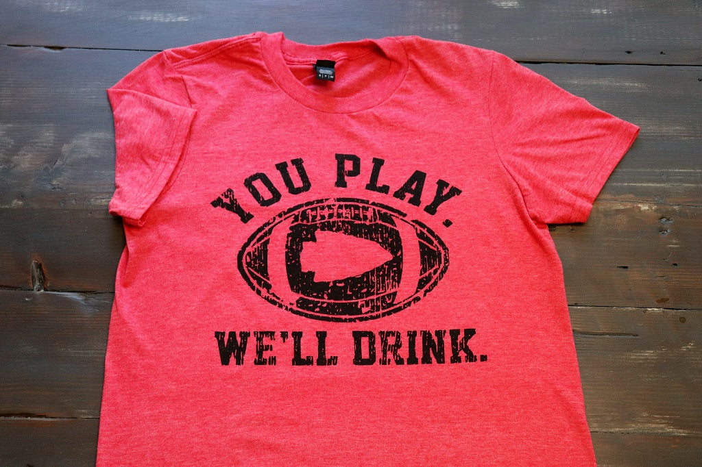 "Kansas City ""You Play We'll Drink"" Featuring an Arrowhead in the middle of a football short sleeve unisex crew neck t-shirt in heather red - Dalton Ink"
