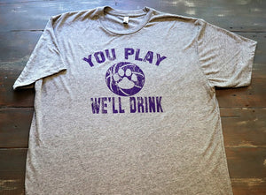 """You Play We'll Drink"" from Kansas State University Manhattan, Kansas printed in purple on a heather grey unisex short sleeve t-shirt - Dalton Ink"