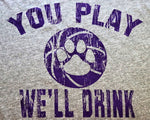 """You Play We'll Drink"" from Kansas State University Manhattan, Kansas printed in purple on a heather grey unisex short sleeve t-shirt close up - Dalton Ink"
