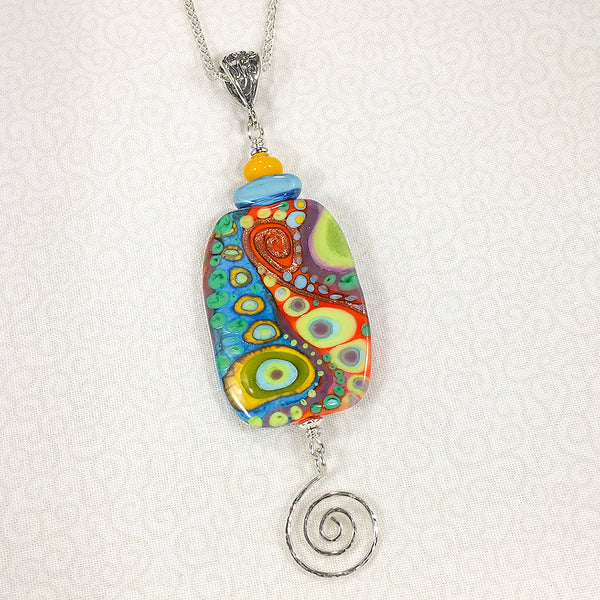 Sterling silver necklace with reversible art glass bead in bright colors and abstract patterns