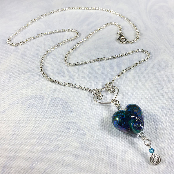 Sterling necklace with iridescent blue art glass heart bead on a handmade heart-shaped pendant