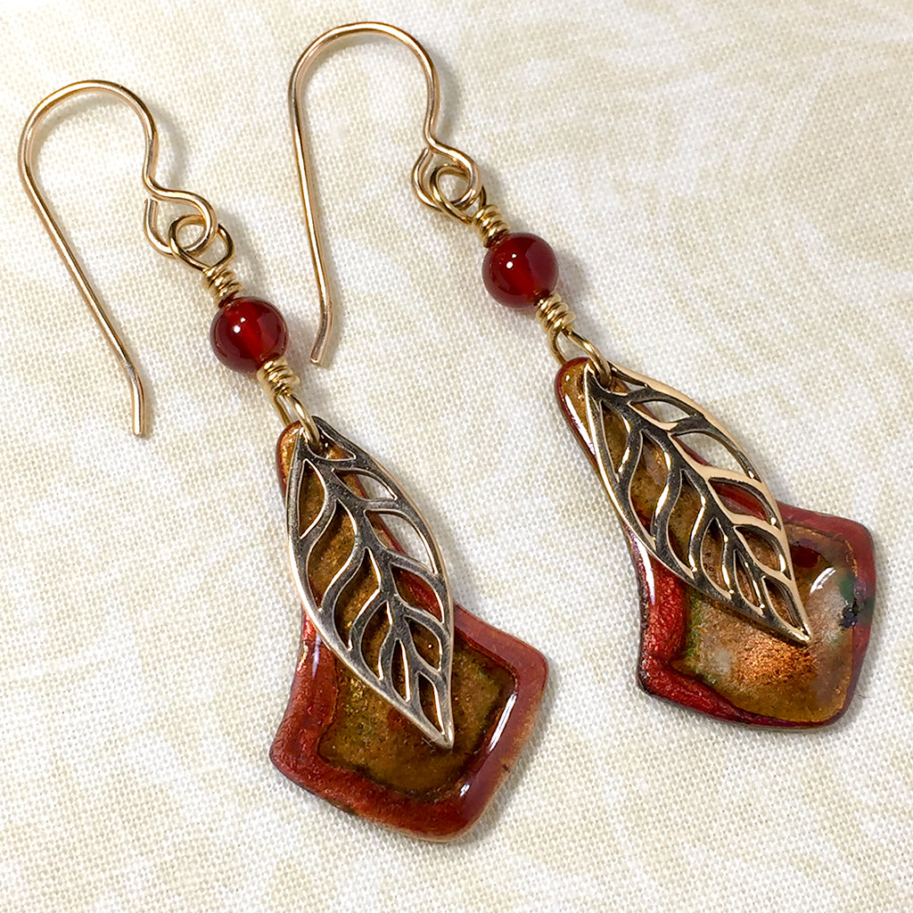Earrings with bronze leaves, copper and russet enameled copper charms, and carnelian beads