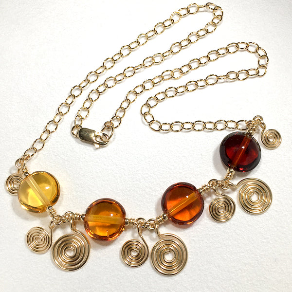 Gold-filled necklace with amber-colored art glass beads and handmade spiral charms