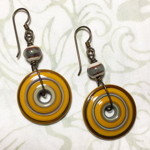 Antiqued brass and niobium earrings with orange art glass discs and earthtone art ceramic beads