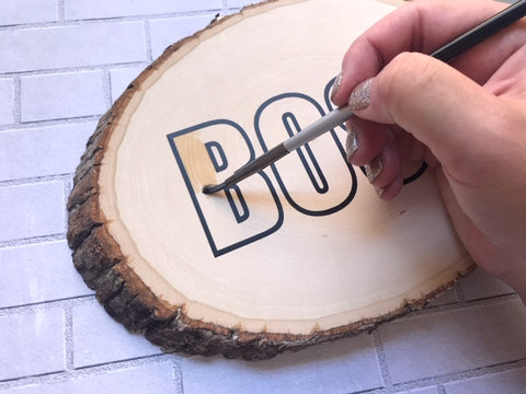 Painting using a brush inside kassa adhesive vinyl on wooden slice