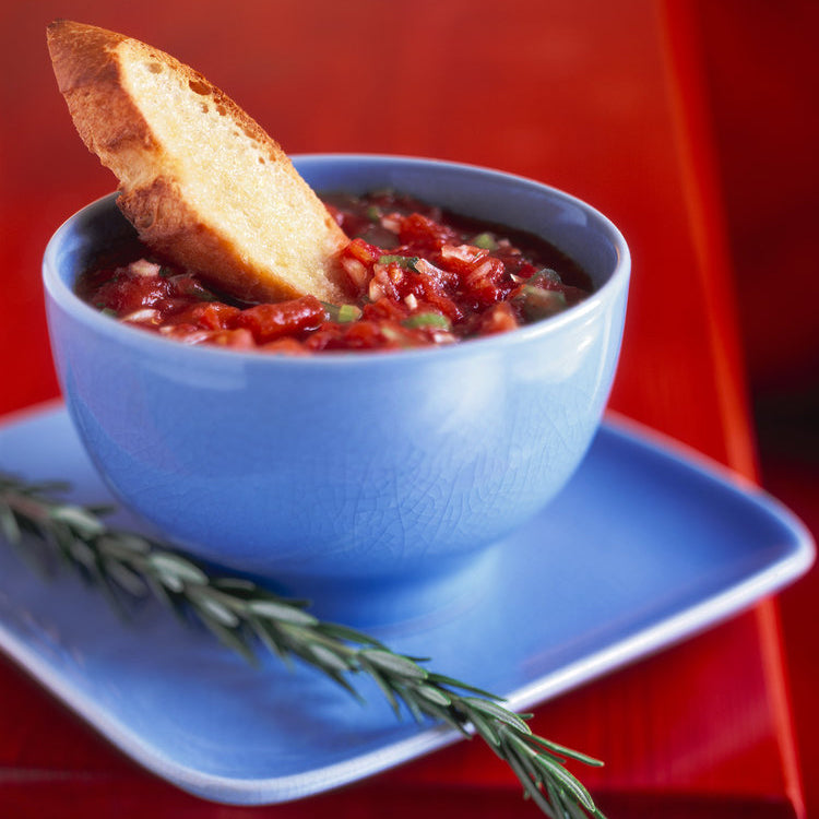 Cup of soup with bread and rosemary sprig on a blue plate and red table. Image by Jeffrey Paul Gunthart. Sarasota, Florida.