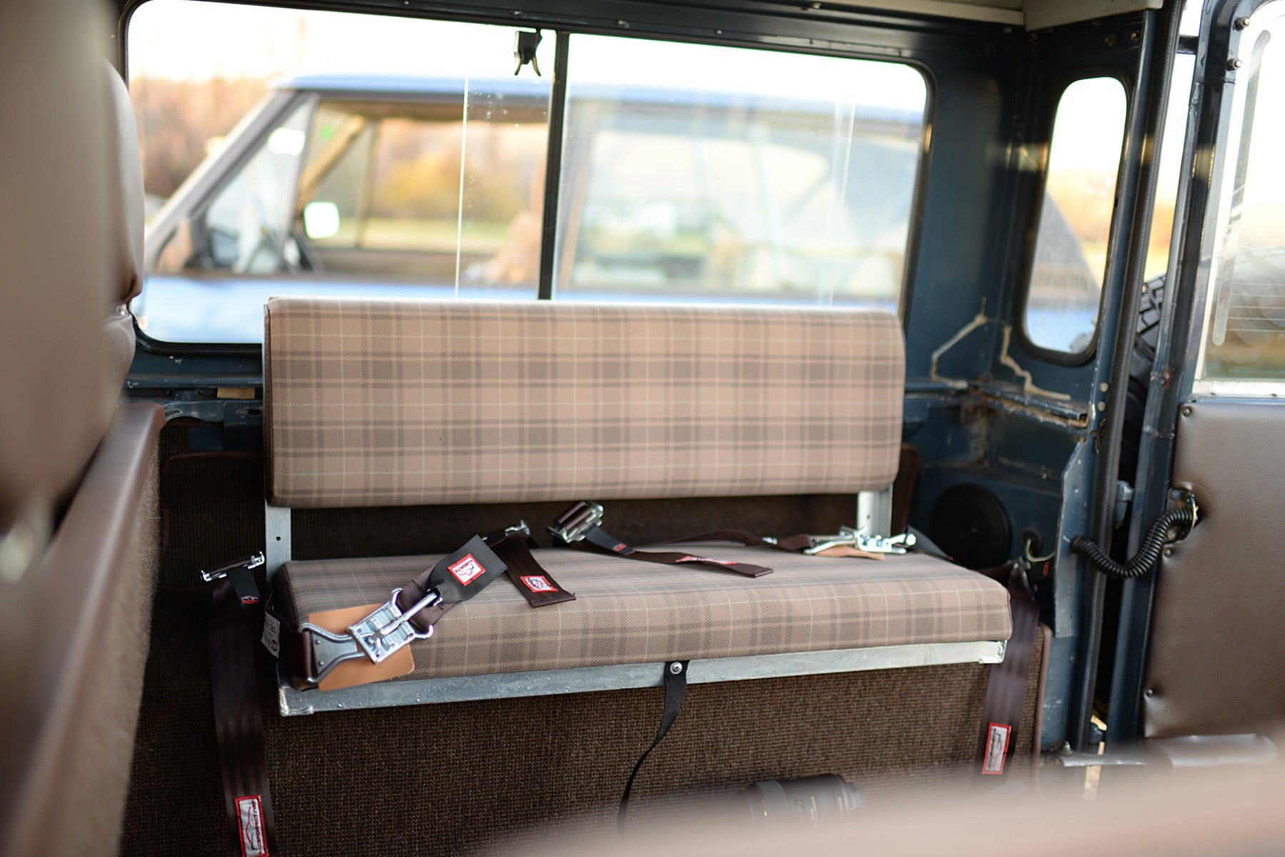Relicate Leather Land Rover Defender interior with plaid cloth inserts rear bench seat