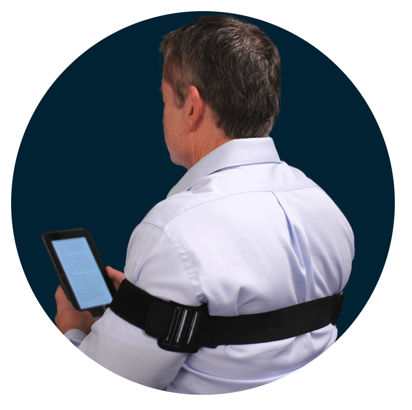 Image of a man wearing a PostureNOW posture corrector holding a tablet