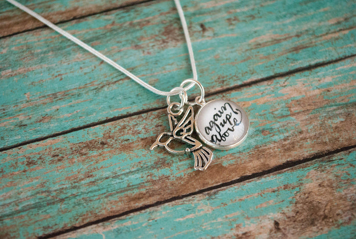"Necklace for someone experiencing miscarriage or child loss. Image shows necklace with a hummingbird charm and a lettered charm.  The chain is sterling silver and 18inches long and the hand lettered charm is 16mm in diameter. Lettered charm reads ""again up above"" and there is also a small metal hummingbird charm, symbolizing the small child lost."