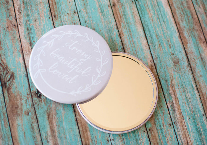 A simple gift to remind her that she is strong, beautiful, and loved.  Grey pocket mirror which is 3.5 inches across with a durable Mylar coating.  The words strong, beautiful, loved are written in white script with a white ivy going around the border of the mirror.
