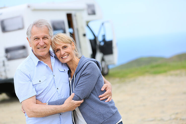 Elder couple hugging infront of RV on the coast. Unique Camping + Marine