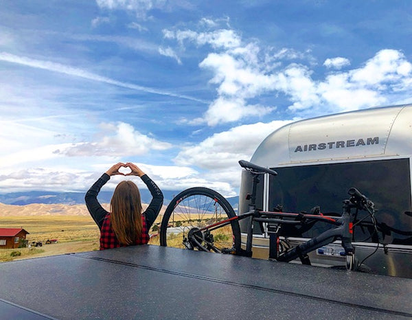Image of Lindsey, Standing next to her airstream, overlooking plains transitioning into foothills, into mountains.
