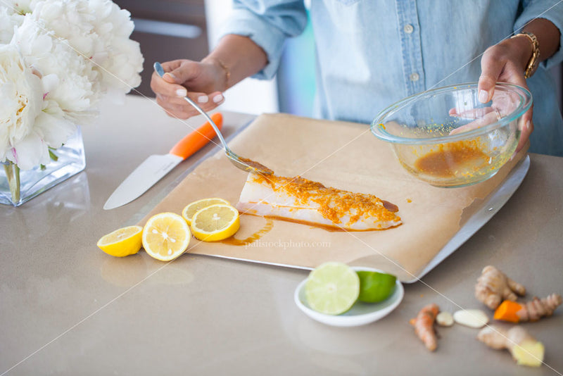 A woman marinating fish before cooking