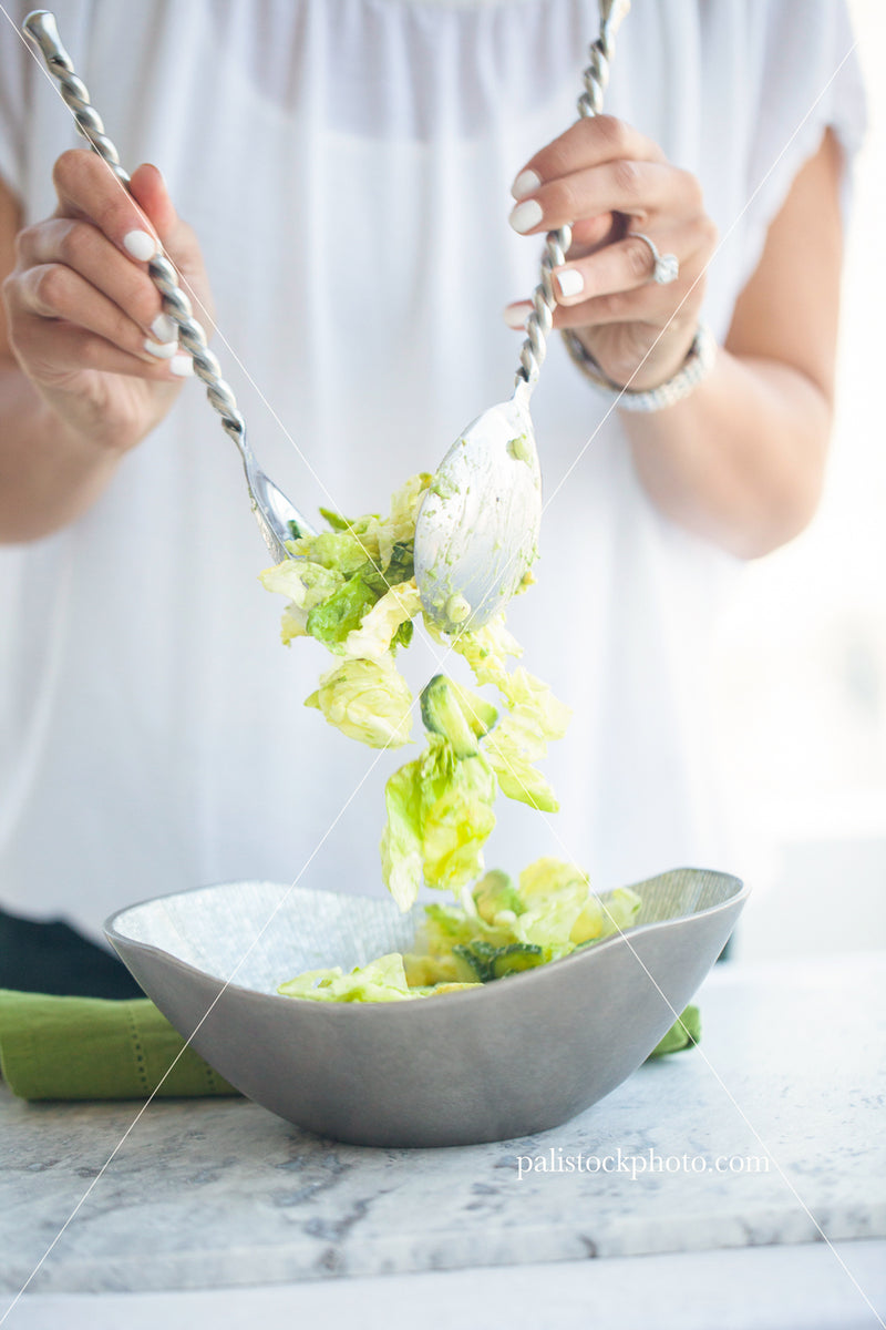 Girl mixing green salad in a bowl
