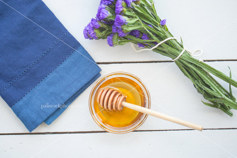 Honey flowers and blue napkin on white wood tabletop