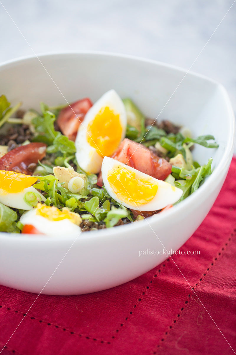 Salad with egg in white bowl on red napkin