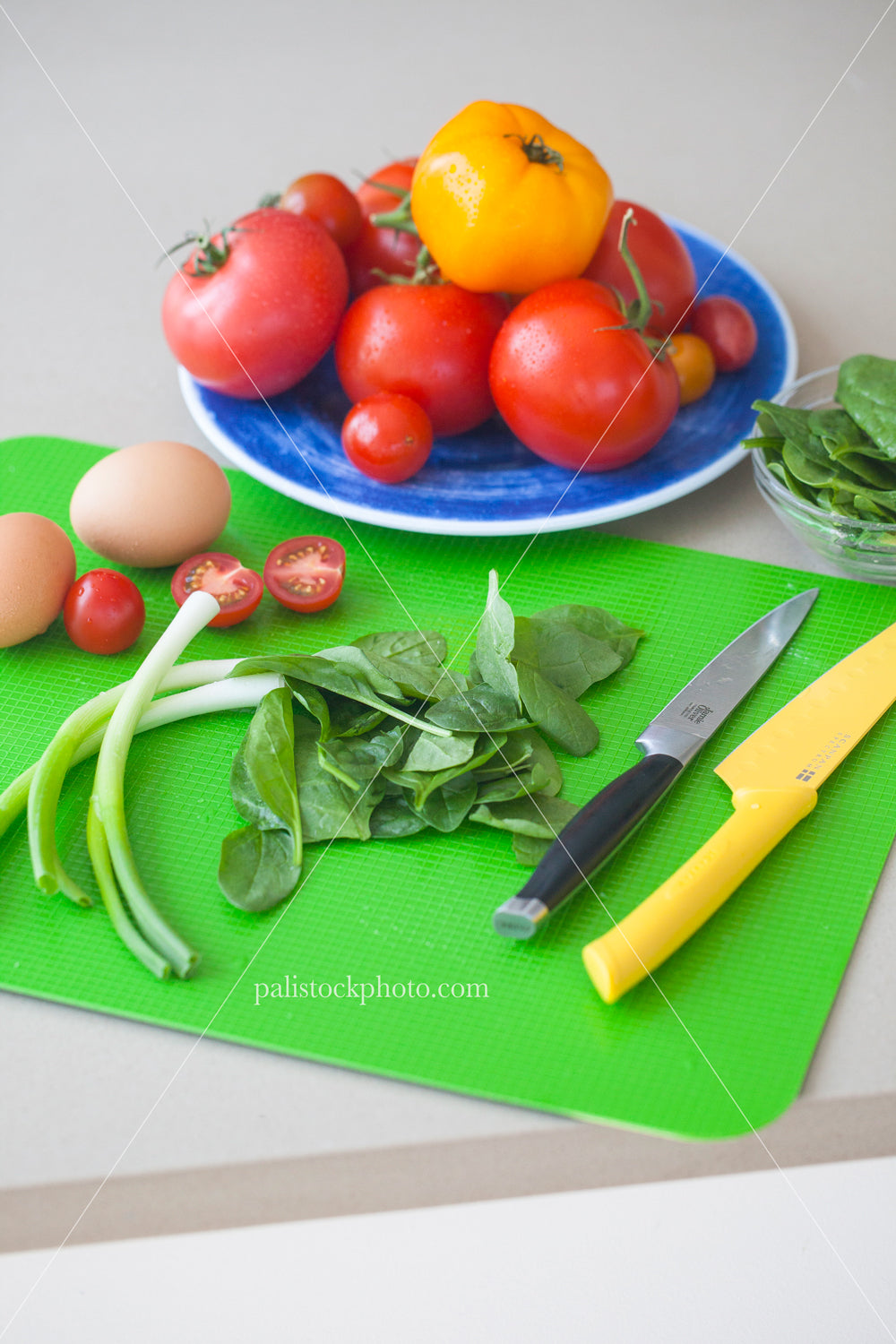 Arrangement of fresh vegetables and eggs on a cutting board vertical