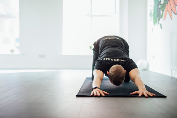 A man performing a yoga stretch in a fitness studio in Belfast.