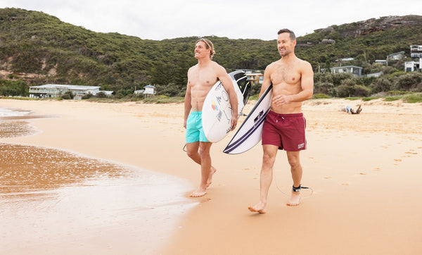 2 surfers at the beach in the Gym+Coffee sustainable swimwear range