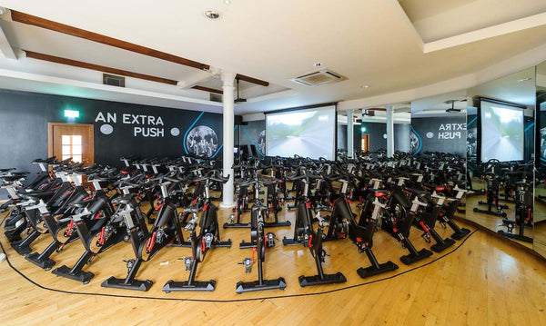 Multiple rows of spinning bikes in a fitness studio.