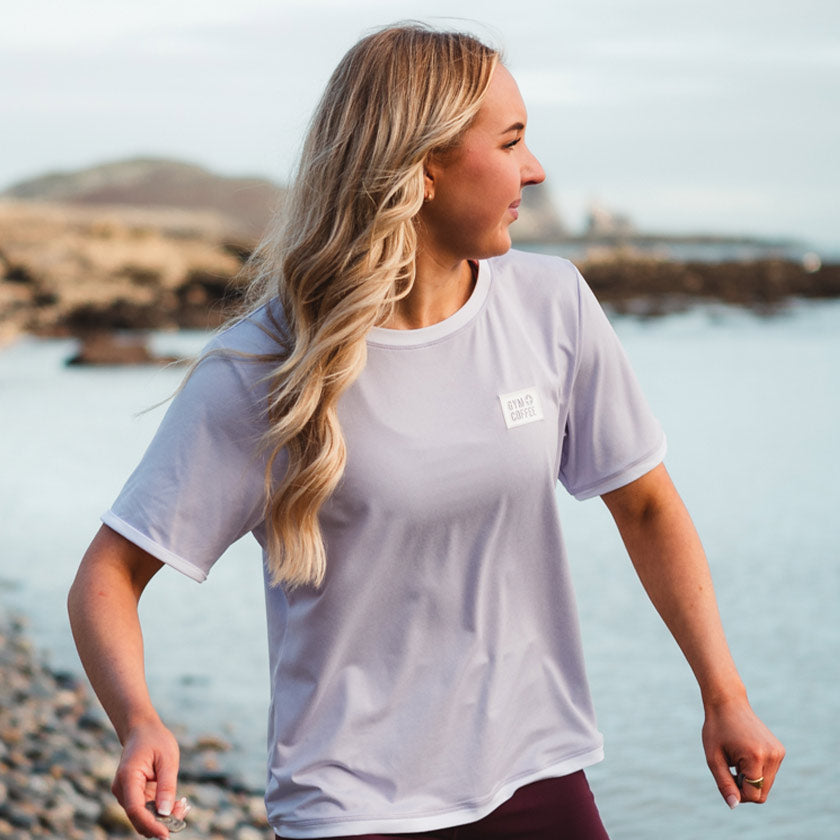 Gym plus coffee shop tees and tanks amarach collection sustainable tee lilac on beach