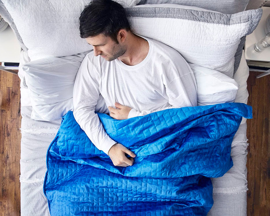 man sleeping with a blue weighted blanket