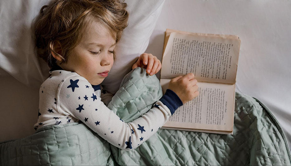 child sleeping with a weighted blanket and an open book