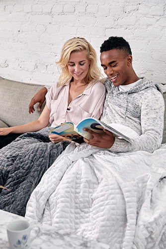 couple cuddling with blankets on couch