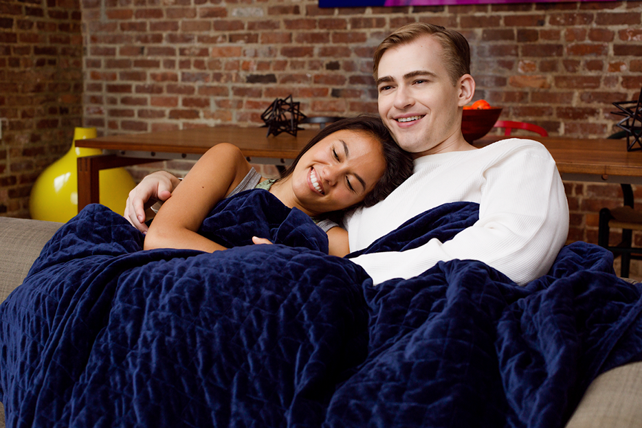 couple snuggling under weighted blanket