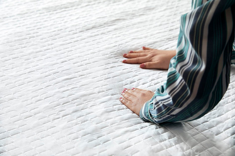 hands smoothing over blanket