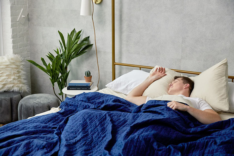man resting in bed with weighted blanket