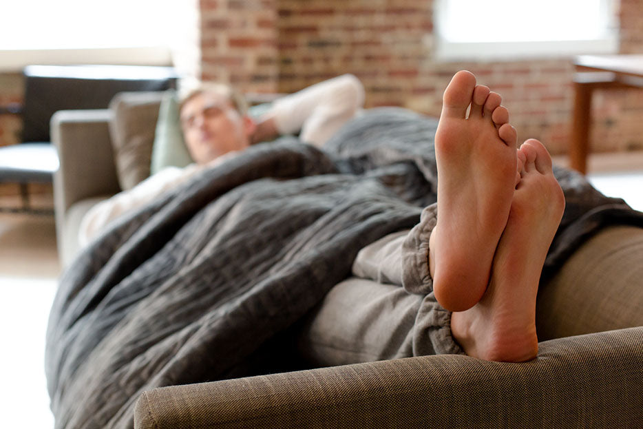 man sleeping on couch with gravity blanket