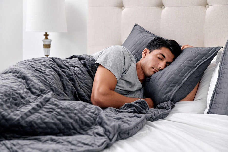 man sleeping with gray weighted blanket