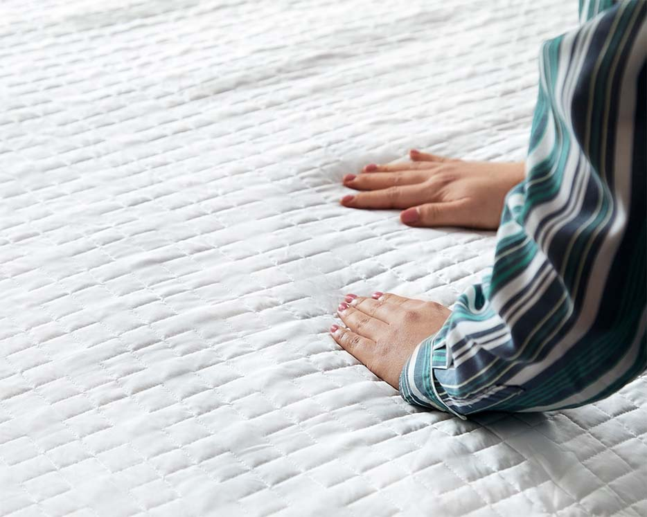 smoothing blankets on bed
