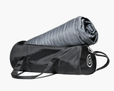 Image of Grey Gravity Travel Blanket sticking out of a black duffel bag.