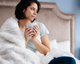 Woman Enjoying Faux Fur Duvet Cover in White in Bed with Coffee