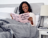 A woman sitting up in bed smiling reading Adventures in Dream State.