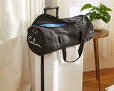 Calm and Gravity Travel Blanket in Calm blue folded in travel bag on top of suitcase