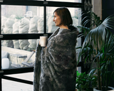 woman looking out window during winter with cup of coffee and wrapped in the faux fur duvet cover