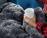 Woman enjoying Faux Fur Duvet in Grey with Coffee