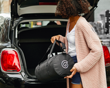 Young woman loading a black Gravity Travel duffel bag into the trunk of a black car.