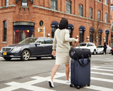 Woman crossing the street with a navy suitcase and black Gravity Travel duffel bag on top.