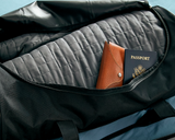 Close up image of Gravity Travel in the black duffel bag. The sipper of the duffel bag is open to show the Travel Blanket, eyeglasses case, and a passport.