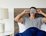 Man holding the weighted sleep mask on.