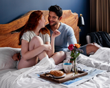 two people eating breakfast in bed on Gravity Bamboo Sheets in white