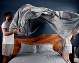 Two people making bed with Gravity Bamboo Sheets in grey