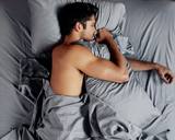 man sleeping in bed using Gravity Bamboo Sheets in grey
